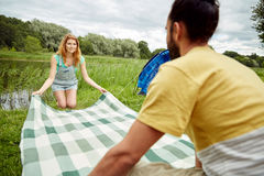 Happy couple laying picnic blanket at campsite Royalty Free Stock Photo