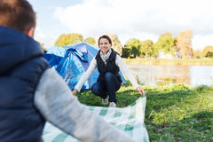 Happy couple laying picnic blanket at campsite. Camping, travel, tourism, hike and people concept - happy couple laying picnic blanket at campsite Royalty Free Stock Photo