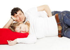 Happy couple laying on red pillow over white. Background Royalty Free Stock Photo
