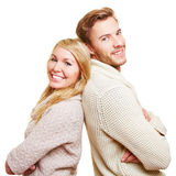 Happy couple leaning back to back Stock Image