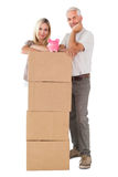 Happy couple leaning on pile of moving boxes with piggy bank Royalty Free Stock Photo