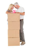 Happy couple leaning on pile of moving boxes with piggy bank Stock Photography
