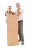 Happy couple leaning on pile of moving boxes Stock Image