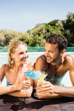 Happy couple leaning on pool edge and toasting with cocktails Stock Photos