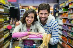 Happy couple leaning on trolley at supermarket. Portrait of happy couple leaning on trolley at supermarket Royalty Free Stock Photography