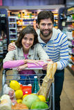 Happy couple leaning on trolley at supermarket. Portrait of happy couple leaning on trolley at supermarket Stock Photography