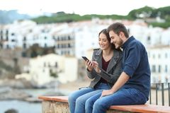 Happy couple on a ledge checking smart phone. With a town in the background stock images