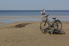 Happy couple left their bicycles on the beach, which they have ridden from holiday accommodation.  stock images