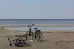 Happy couple left their bicycles on the beach, which they have ridden from holiday accommodation royalty free stock photo