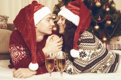 Happy couple lie near xmas tree and decoration at home. Winter holiday and love concept. Yellow toned. Royalty Free Stock Photo