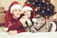 Happy couple lie near xmas tree and decoration at home. Winter holiday and love concept. Yellow toned. Royalty Free Stock Images