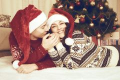 Happy couple lie near xmas tree and decoration at home. Winter holiday and love concept. Yellow toned. Stock Photos