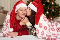 Happy couple lie under blanket near xmas tree and decoration at home. Winter holiday and love concept. Stock Photo