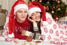 Happy couple lie under blanket near xmas tree and decoration at home. Winter holiday and love concept. Stock Image