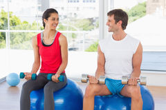 Happy couple lifting dumbbells while sitting on fitness balls in gym Royalty Free Stock Photography
