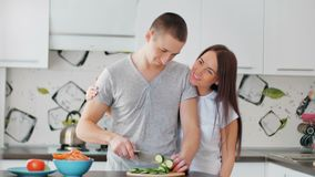 Happy couple on the light kitchen cooking together. Young woman shreding vegetables to prepare healthy lunch. Vegan Salad. Diet. Dolly Shot stock footage