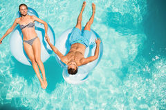 Happy couple on lilos. In the pool royalty free stock photo