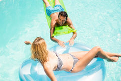 Happy couple with lilos in the pool. In a sunny day Stock Images