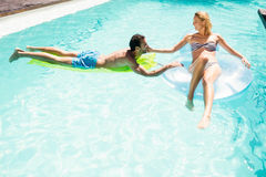 Happy couple with lilos in the pool Royalty Free Stock Photography