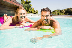 Happy couple with lilos in the pool Stock Image