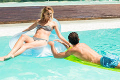 Happy couple with lilos in the pool Stock Photos