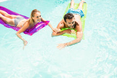 Happy couple with lilos in the pool. In a sunny day Stock Photo