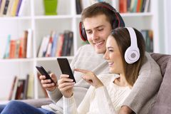 Happy couple listening to music on line at home. Happy couple listening to music on line with their smart phones sitting on a sofa at home Royalty Free Stock Photography