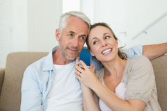 Happy couple listening to phone call together on the couch Stock Photos