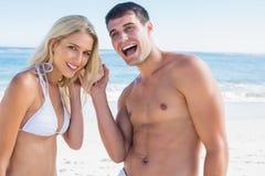 Happy couple listening to seashell Stock Photo