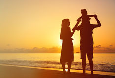 Happy couple with little child at sunset beach Royalty Free Stock Image