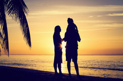 Happy couple with little child at sunset beach Stock Images