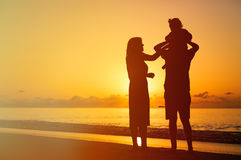 Happy couple with little child at sunset Royalty Free Stock Photography