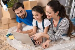 Happy couple with little daughter lying on bubble wrap, looking at laptop screen in repairing house. stock photo