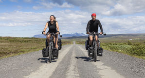 Happy couple on loaded bicycles Royalty Free Stock Photography