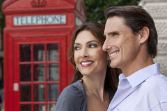 Happy Couple In London With Red Telephone Box. A romantic happy man and woman couple in London, England, with a classic red telephone box out of focus behind him Royalty Free Stock Image