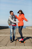Happy couple with longboard riding outdoors Royalty Free Stock Photos