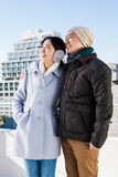 Happy couple looking away. Against buildings Stock Images