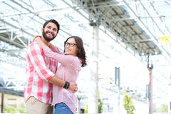 Happy couple looking away while embracing outside building Royalty Free Stock Image