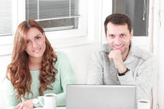 Happy couple looking at camera with laptop at home. Happy couple relaxing using the laptop and smiling at camera at home and sitting in living room with cup of royalty free stock photography