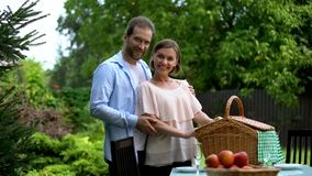 Happy couple looking at camera, preparing for picnic, social welfare, wellness. Stock photo royalty free stock photography