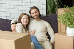 Happy couple looking at camera sitting on sofa, moving day. Happy couple looking at camera sitting on sofa embracing on moving in out day, smiling men and women Royalty Free Stock Photos