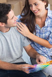 Happy couple looking at color samples to decorate their house Royalty Free Stock Images