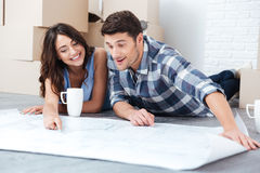 Happy couple looking at construction house plan Royalty Free Stock Photography