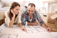 Happy couple looking at construction plan Royalty Free Stock Photos