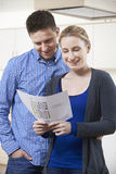 Happy Couple Looking At Details For Property They Hope To Buy Royalty Free Stock Photography