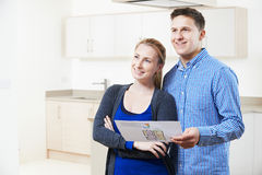 Happy Couple Looking At Details For Property They Hope To Buy stock images