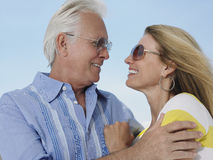 Happy Couple Looking At Each Other Against Sky. Happy middle aged couple wearing sunglasses while looking at each other against sky Royalty Free Stock Photos