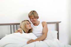 Happy couple looking at each other in bed Stock Photography