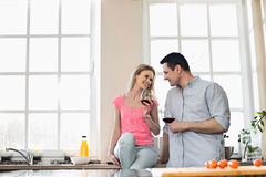 Happy couple looking at each other while drinking red wine in kitchen Royalty Free Stock Photos