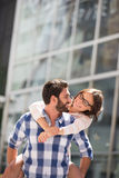 Happy couple looking at each other while enjoying piggyback ride in city Stock Photography